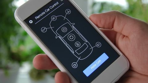 Man remotely parking his car. Car remote control using smartphone application fictional interface.