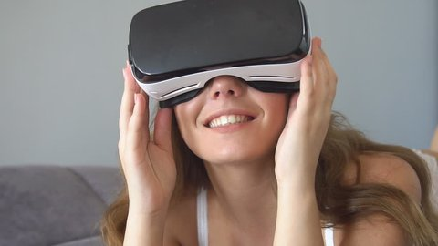 Young blonde woman playing game using VR-helmet for smart phones. Augmented reality device allows to deep into virtual space