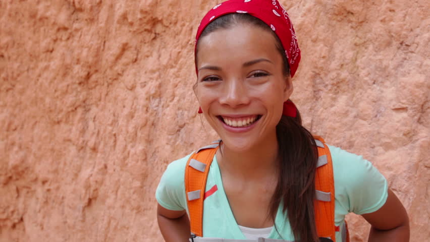 Beautiful smiling girl wearing backpack on hike