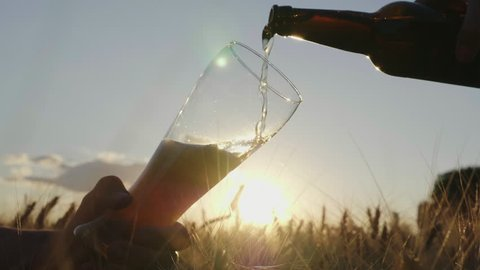 Pour the beer into the glass from the bottle. On a wheat field at sunset. Slow motion video