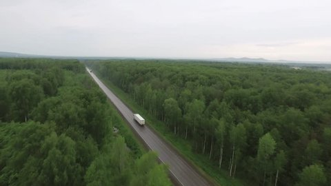 Trucks driving / traveling on highway in forest, aerial footage / top view / Highway truck traffic