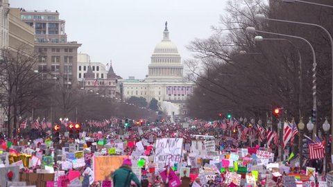 Washington D.C.-2010s: Huge crowds of protestors chant, wave flags, hold signs and march in Washington D.C. in a massive anti-Trump rally.