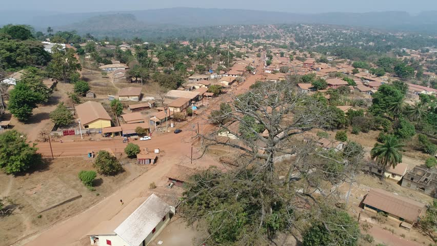 Aerial over the west African city Télimélé in Guinea, drone view over the poor township and  little huts with landscape in background