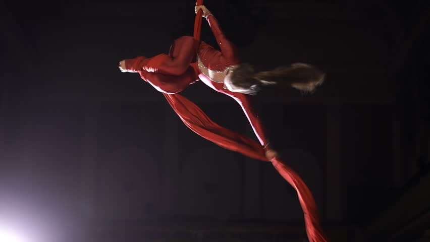 Female aerial gymnast performing on a red silk in a circus stage. Exciting acrobatic show.