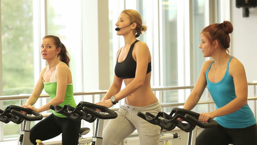 Group of sporty women training with instructor in center