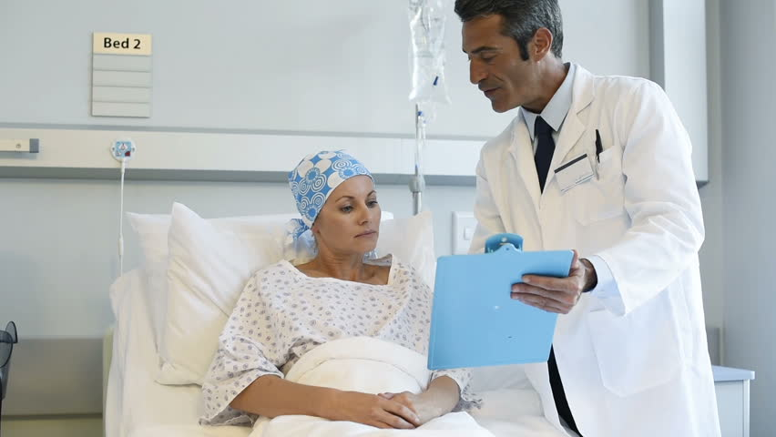 Doctor telling to patient woman the results of her medical tests. Doctor showing medical records to cancer patient in hospital ward. Senior doctor explain the side effects of the intervention. | Shutterstock HD Video #28765792