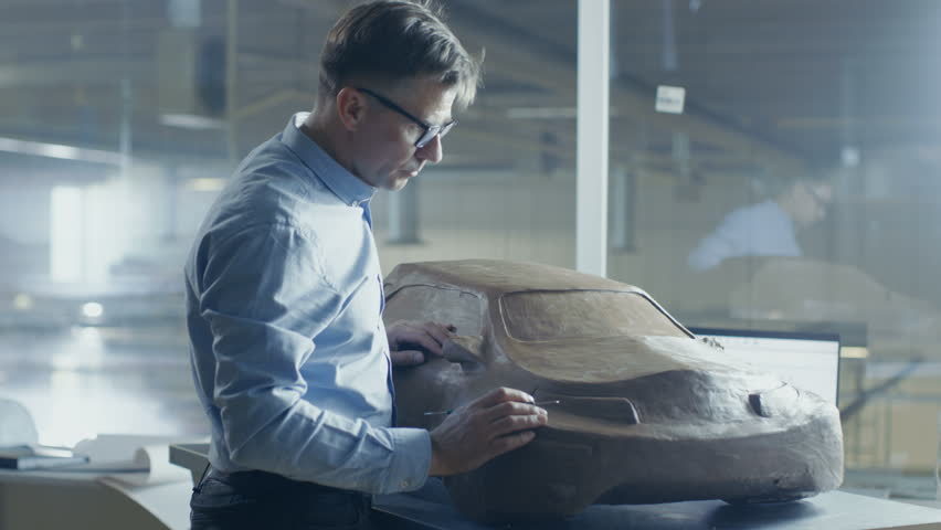 Senior Automotive Designer with Rake Sculpts Futuristic Electric Car Model from Plasticine Clay. He Works in a Special Studio Located In a Large Car Factory.Shot on RED EPIC-W 8K Helium Cinema Camera.