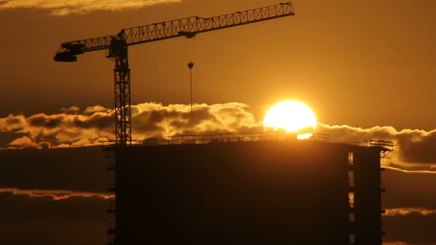Silhouettes of workers on construction site at background sunset sun on cloudy sky | Shutterstock HD Video #28769902