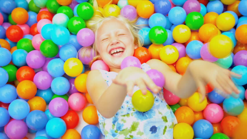 Pretty blonde Caucasian girl having fun lying in multi coloured ball pool shot on RED EPIC