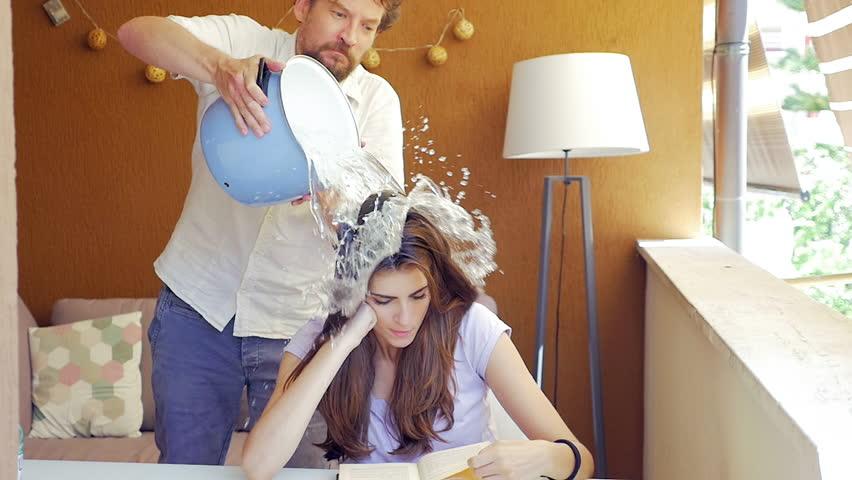 Man making joke to girlfriend splashing bucket of cold water on head slow motion