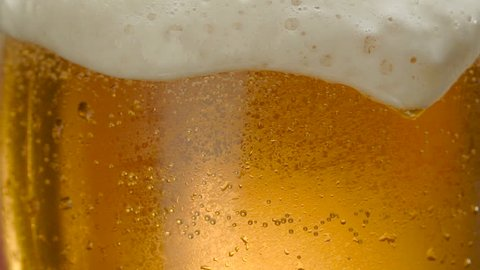 Glass of beer close-up with froth in slow motion