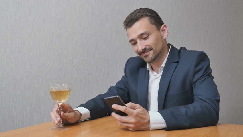 Businessman enjoys the Internet while drinking an alcoholic drink. Person celebrating something looking in smartphone. Man with a glass of wine online | Shutterstock HD Video #28820806