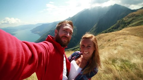 Young couple hiking, taking a selfie on mountain peak Cheerful young couple hiking in summer taking a selfie on mountain top.