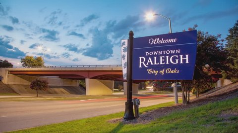 Welcome to Downtown Raleigh - City of Oaks Sign Timelapse with Passing Vehicle Traffic Driving at Sunset during the Summer in North Carolina