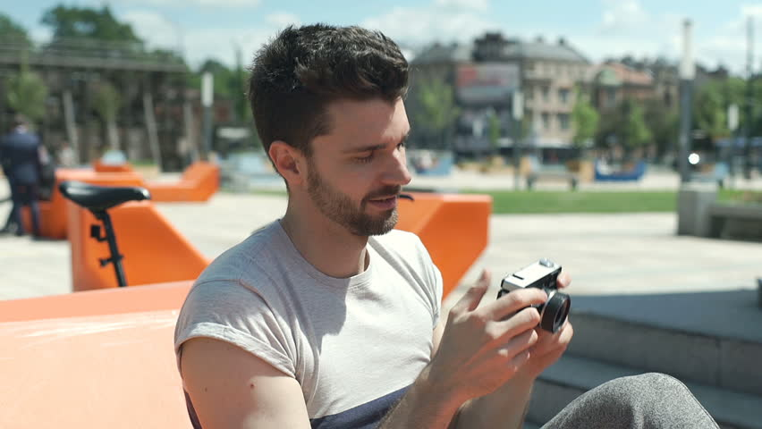 Handsome man sitting on the orange seat in the city and doing photos on old camera, steadycam shot  | Shutterstock HD Video #28850992