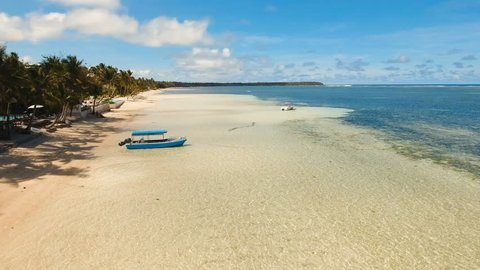 Beautiful tropical island with sand beach, palm trees. Aerial view of tropical beach on the island Siargao, Philippines. Tropical landscape: beach with palm trees. Seascape: Ocean, sky, sea