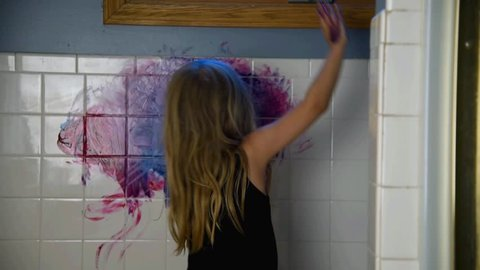 A little child is painting on a bathroom wall making a mess for a funny parenting discipline concept.
