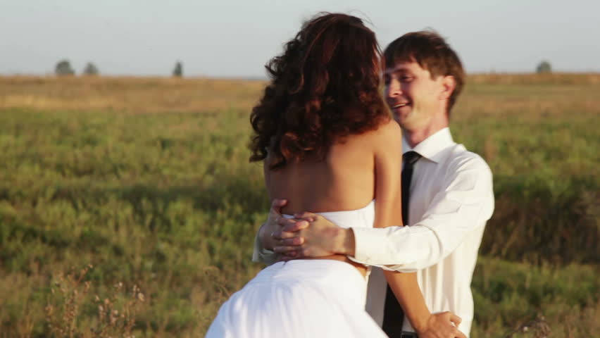 Married couple dance at sunset. The groom lifts the bride and turns her