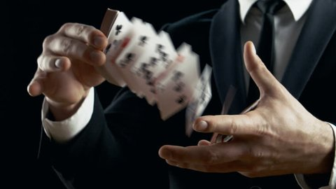 Close-up of a Magician's Hands Performing Card Trick. Throwing and Catching Cards in the Air. Background is Black. Slow Motion. Shot on RED EPIC-W 8K Helium Cinema Camera.