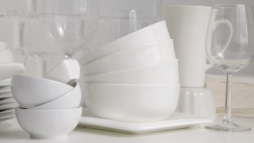 Stacked white porcelain dishes, plates, cups, saucers, mugs in restaurant kitchen interior. Slow pan. White brick wall background.	Selective focus. | Shutterstock HD Video #28921612