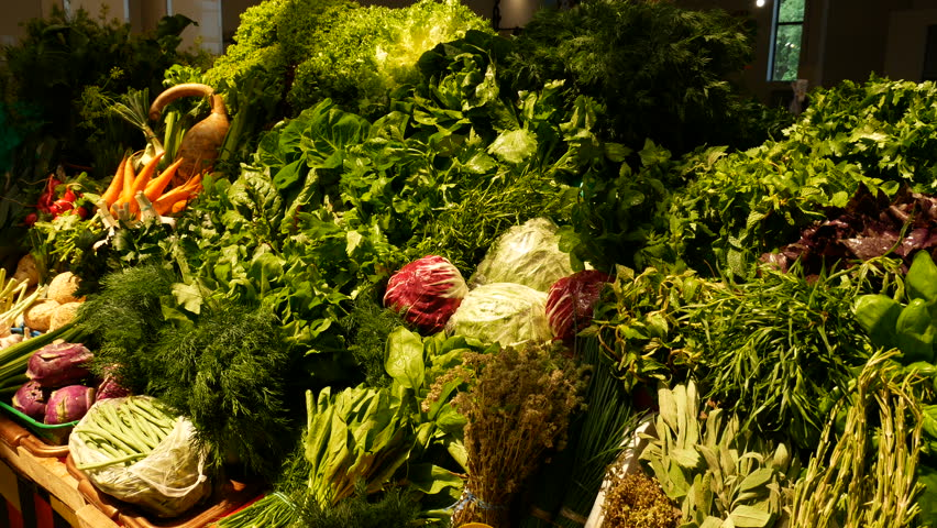 Close-up a lot of cabbedge, carrots, parsley, spinach, basil, rennel, dill, tarragon, and melissa at the counter at the market