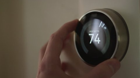 Man Adjusting Smart Thermostat Gadget Settings At Home