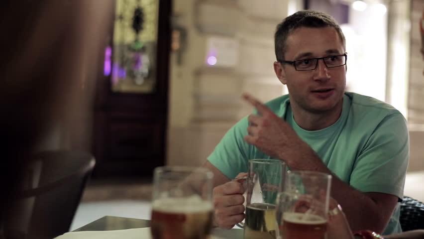 Three friends in restaurant drinking beer in the evening, steadycam shot