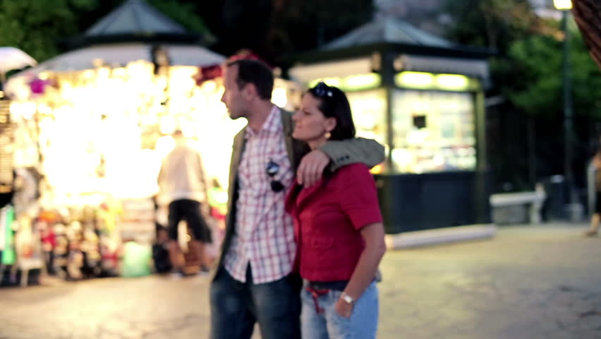 Young couple walking together in night city, steadycam shot