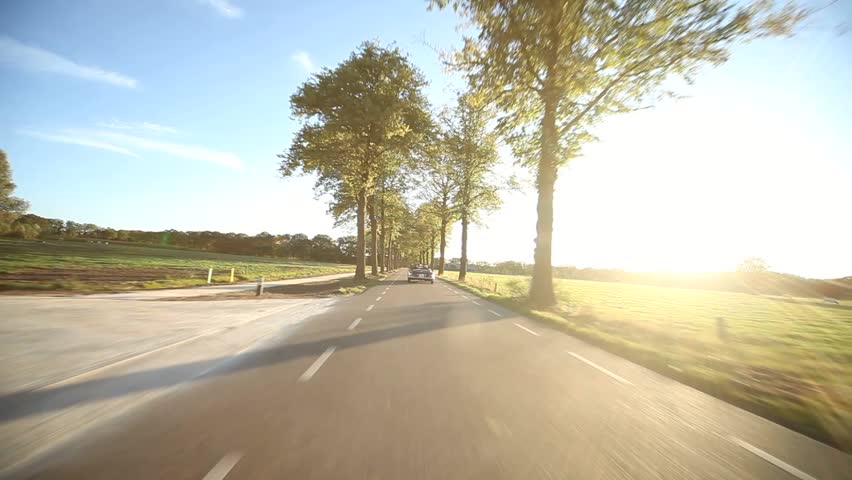 Video footage of a on-board camera on a car driving on a country road in the sunset
