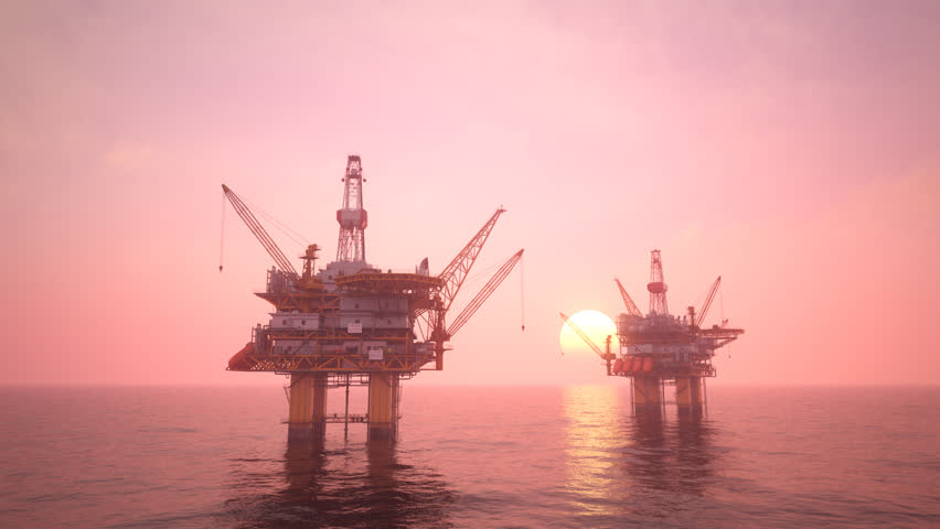 Two offshore platforms or oil rigs at sunset pink sky