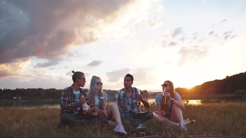 Young happy friends sitting on the grass, talking to each other, laughing, cheerfully toasting, drinking beer and eating fried marshmallows while having the picnic in the nature.