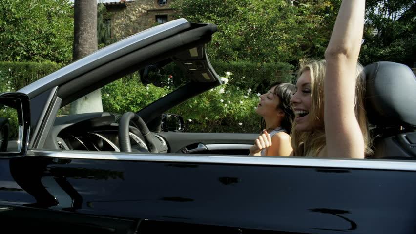 California, USA - April 2017: Beautiful young European friends tossing hair dancing and singing enjoying summer sun in luxury open top car #28983622