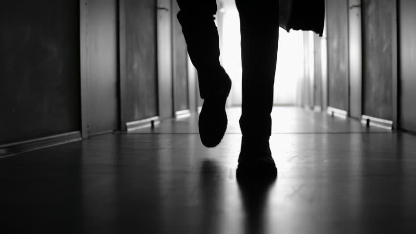 Tracking with low-section of silhouette of legs of man with briefcase walking along dark corridor; black and white slow motion shot