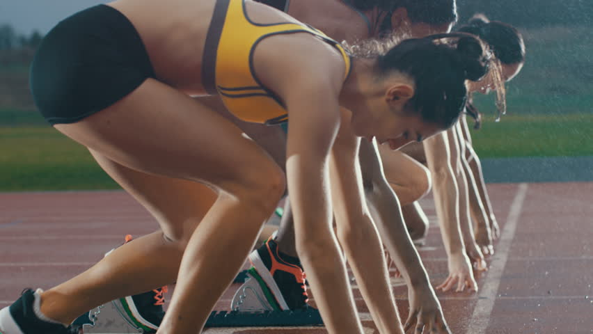 Female runners at athletics track crouching at the starting blocks before a race. In slow motion. #29016952