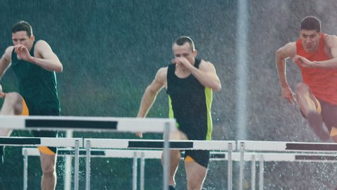 Competitive athletes running & jumping over hurdles at athletics track in slow motion
