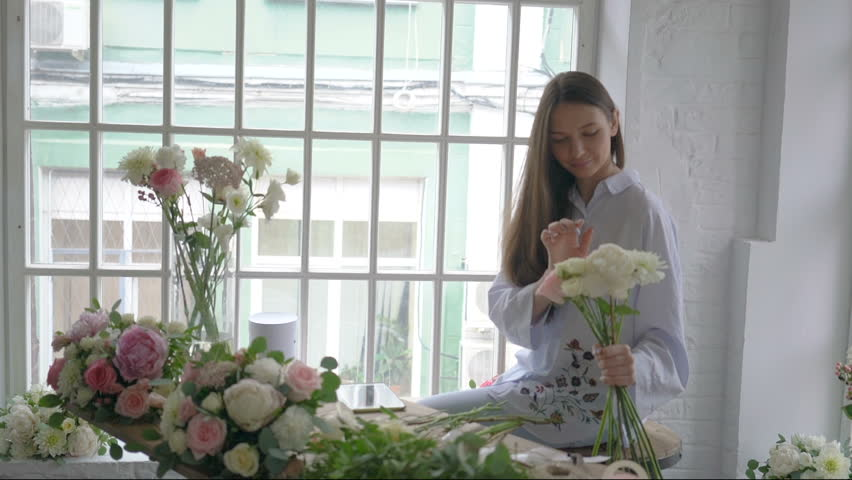 Young florist girl counting bouquet cost using tablet at her flower studio | Shutterstock HD Video #29032162