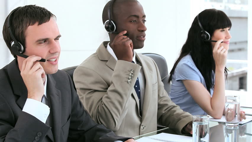 office centre video. happy call centre agents working together with headsets in a bright room hd stock video office