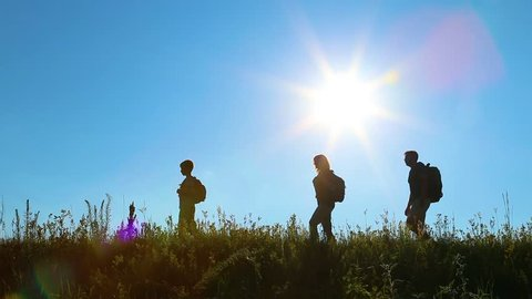 Young healthy family on summer vacations in countryside. Silhouettes of father, mother and 10 years old son hiking. People walking along grassy hill at bright sunset sunlight and blue sky background.