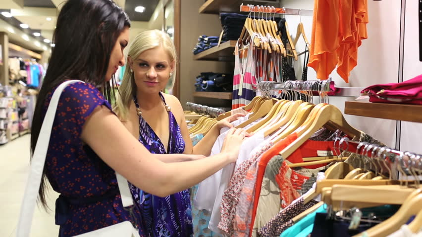 Friends happily shopping together in clothing store