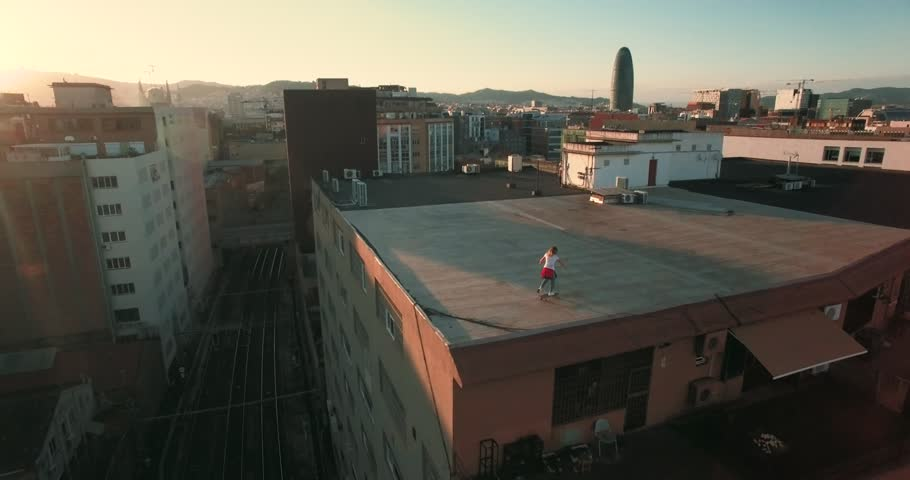Young millenial teenager girl riding her surfskate on big roof top of big industrial building at sunset evening time, aerial shot with peaceful mood