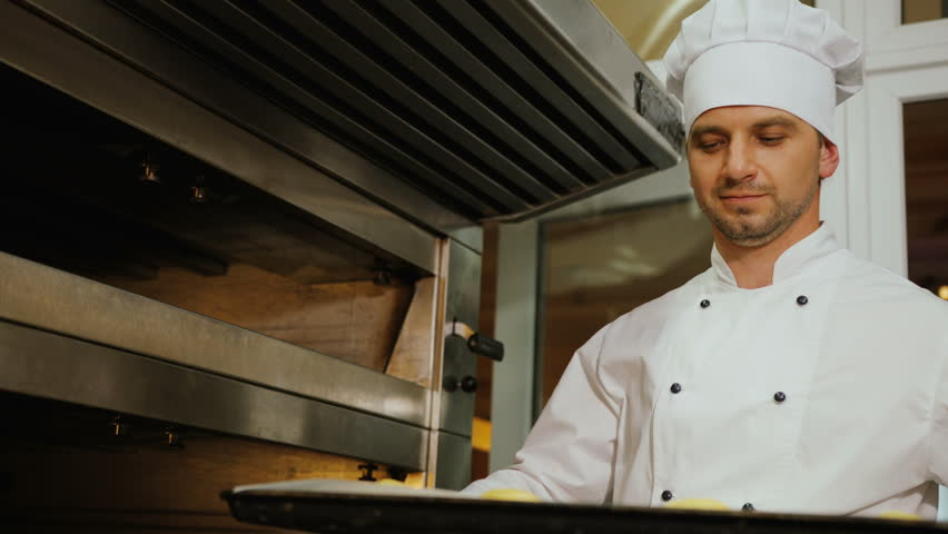 Portrait of young man in the uniform putting breads to the oven. | Shutterstock HD Video #29052763