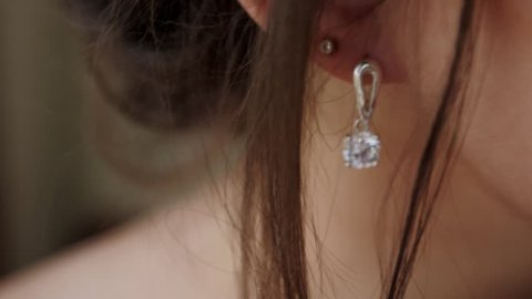 The young woman puts on beautiful earrings