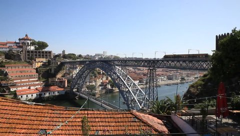 Iron bridge in Porto with view of the river and rooftops with metro passing by