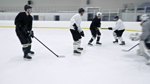 Tracking of ice hockey player in white uniform dribbling puck and doing reverse pass to teammates during practice in rink