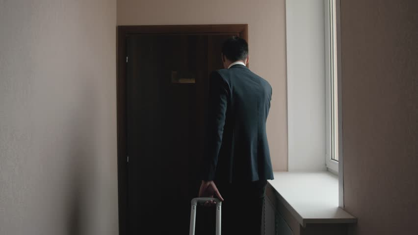 Businessman with his suitcase coming to hotel room looking at the window. Handsome man business travel, living in modern hotel, luggage and suitcase