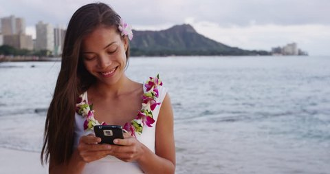 Happy young woman using smartphone at Waikiki Beach. Smiling female tourist is wearing orchid lei garland during vacation at island in Honolulu. She is text messaging using mobile phone on shore.