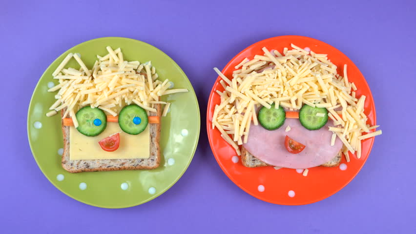 Back to school fun lunches concept, making childrens faces sandwiches on bright colorful background, time lapse.