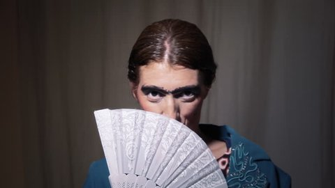 An ugly woman hiding her face behind a fan, and slowly appearing.