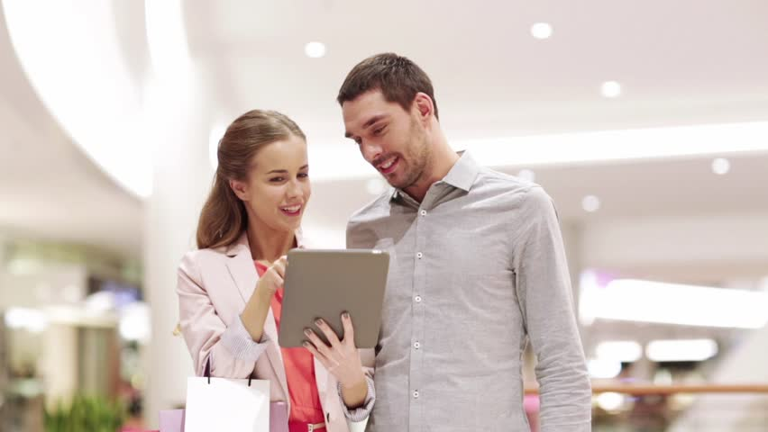 Sale, consumerism, technology and people concept - happy young couple with shopping bags and tablet pc computer talking in mall | Shutterstock HD Video #29140642