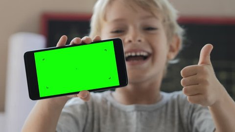 Cute child showing phone with green screen, laughing and showing thumbs up. Idea of very funny video or picture on display.